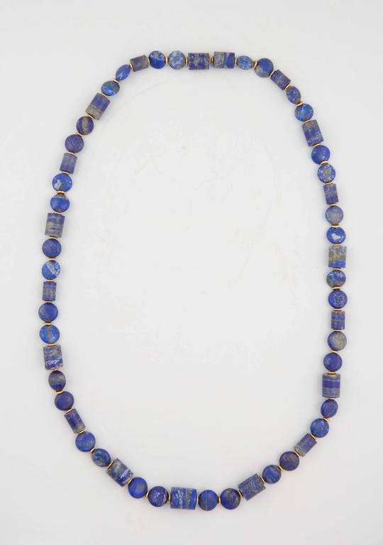 A honed lapis lazuli bead necklace composed of carved lapis lazuli tube beads and carved lapis lazuli smartie beads. The beads are separated by 18kt yellow gold rondelles. Length: 45 inches.