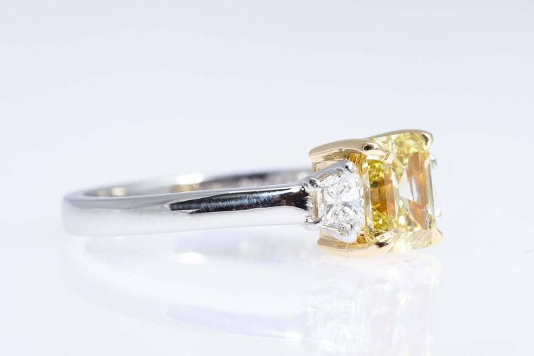 """This emerald cut diamond weighs 1.62 carats and has a GIA certificate stating that it is """"Fancy Intense Yellow"""" and """"VS1"""" in clarity.  The ring is platinum with the center stone mounted in eighteen karat yellow gold. The center"""