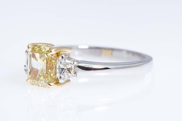 Modern GIA Intense Yellow 1.62 Carat Emerald Cut Diamond Platinum Three-Stone Ring For Sale