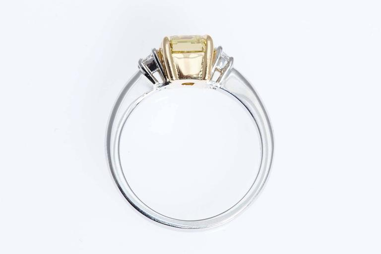 GIA Intense Yellow 1.62 Carat Emerald Cut Diamond Platinum Three-Stone Ring In Excellent Condition For Sale In New York, NY