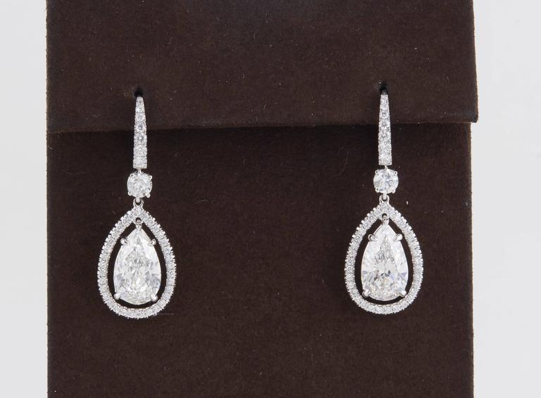 An exceptional pair of earrings featuring two 3 carat each, high quality GIA certified pear shape diamond drops.   The drops are set with 1.33 carats of round brilliant cut diamonds all G color VS clarity.   Two pear shapes weighing a total of