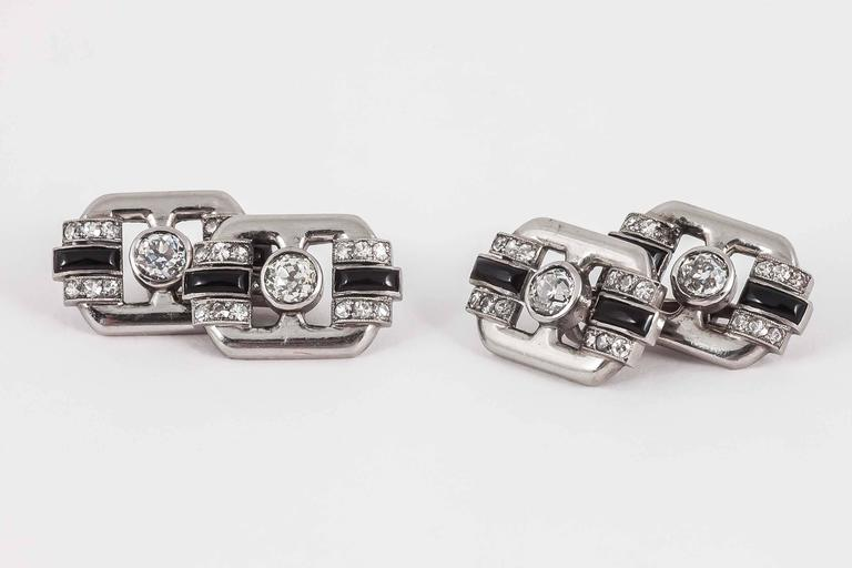 A heavy pair of platinum mounted cufflinks,of openwork,Art Deco period,with an old cut diamond centre,and onyx set at either end with three,small diamonds either side.French marked,c,1930-5