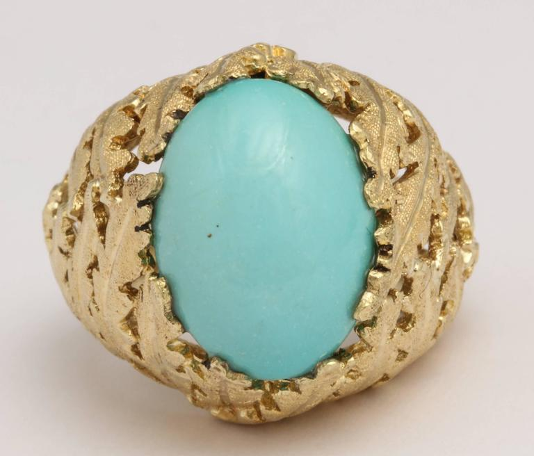 Beautiful 18kt Yellow Gold Foliate mounting set with Persian Turquoise oval cabochon stone.   Beautifully engraved.  Size 5 but can be made larger or smaller