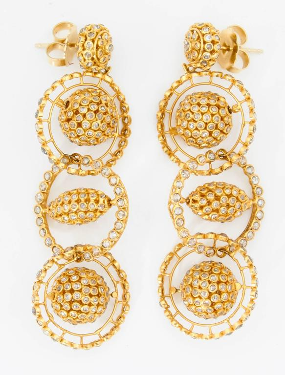 A pair of 18kt yellow gold and rose cut diamond earrings. Each earring is composed of 3 bezel set rose cut diamond rings suspended from a rose cut diamond stud. Each ring has a bar running through the center with a moveable diamond bead. Approximate