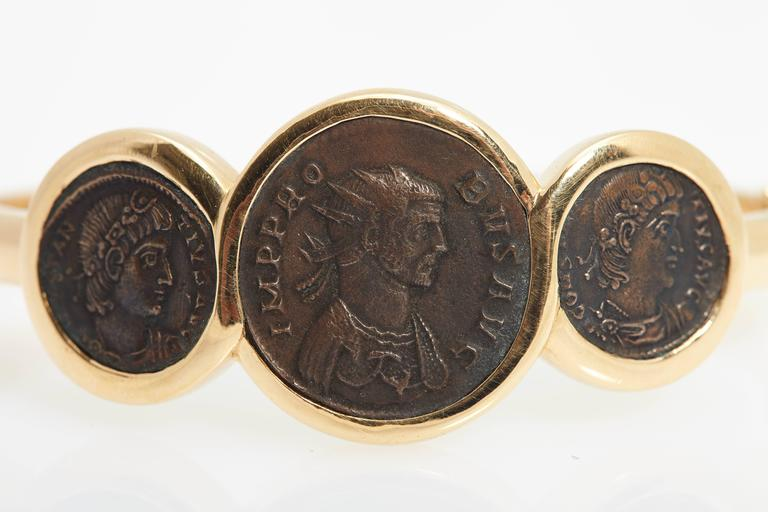 "An unusual yet iconic Bulgari bracelet from the ""Monete Collection"", circa 1975, made in 18kt yellow gold and showcasing three ancient Roman coins, the dates engraved on the back of their respective setting as follows (left to right):  -"