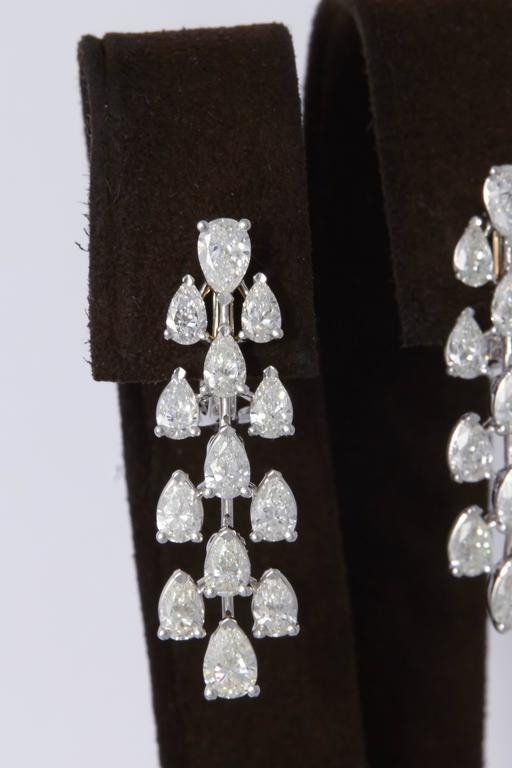An elegant pair of diamond dangle earrings.   5.28 carats of G VS pear shaped diamonds set in 18k white gold.  Approximately 1.35 inches in length.