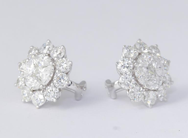 A gorgeous pair of earrings! A unique design!  The center diamonds are made up of special cuts to form a large round diamond illusion.   The round center is then surrounded by halo made up of actual round brilliant cut diamonds.   Total carat