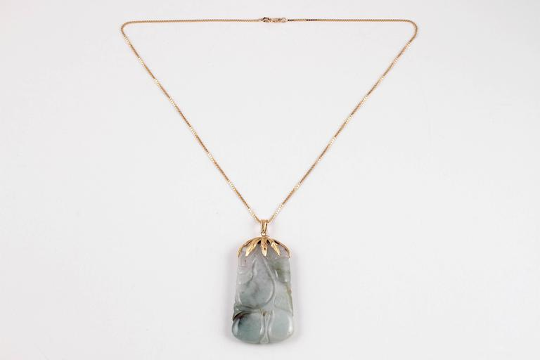Carved jade and 14 karat yellow gold pendant suspended on 20 inch 14 karat box chain.