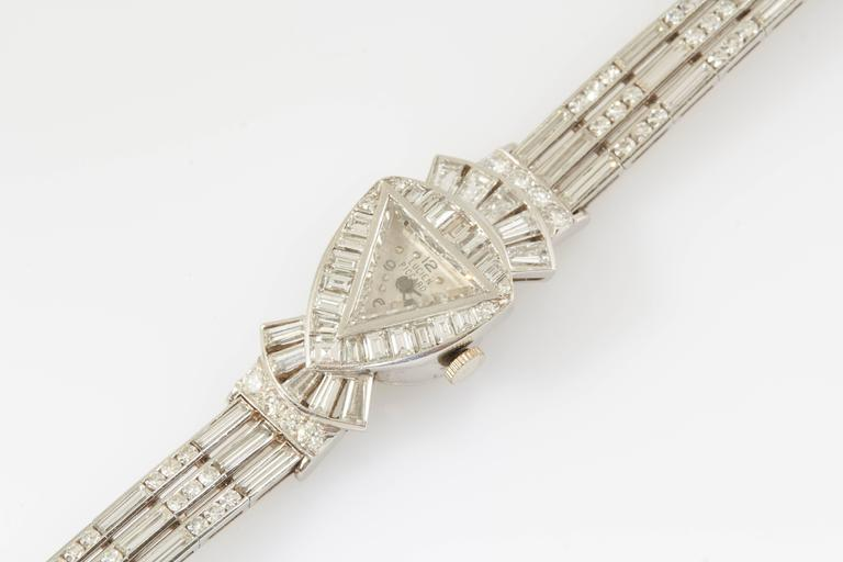 Signed Lucien Piccard watch is composed of baguette and round cut diamonds weighing approximately 20.50 carats in total. The dial is protected by a triangle shaped diamond crystal.