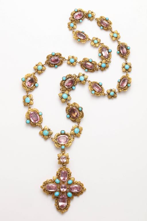 English, Georgian foiled back necklace in 15kt yellow gold. Alternating links of ovals set with pink topaz and turquoise on either side and a floral motif with a central turquoise. A pink topaz and turquoise cross pendant hangs from a connector link