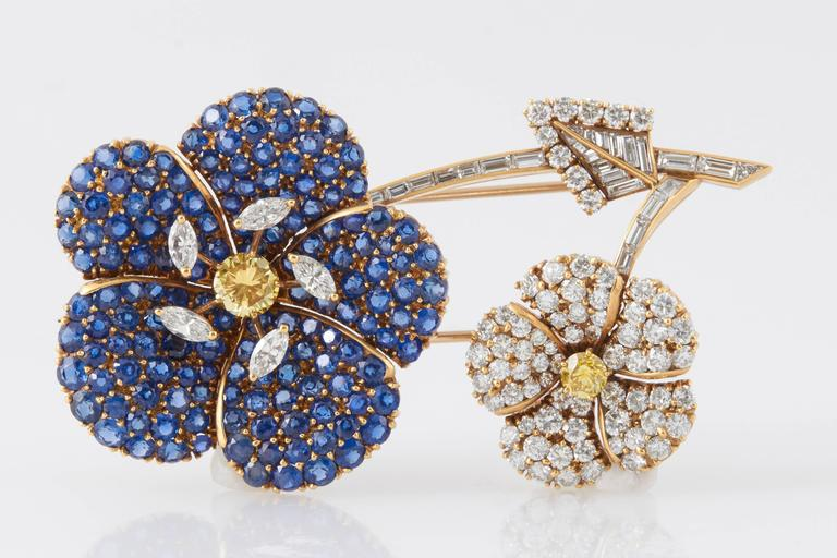 Signed Cartier Flower Brooch finely crafted in 18K yellow gold, accented with sapphires, natural fancy yellow diamonds, round and baguette cut diamonds.