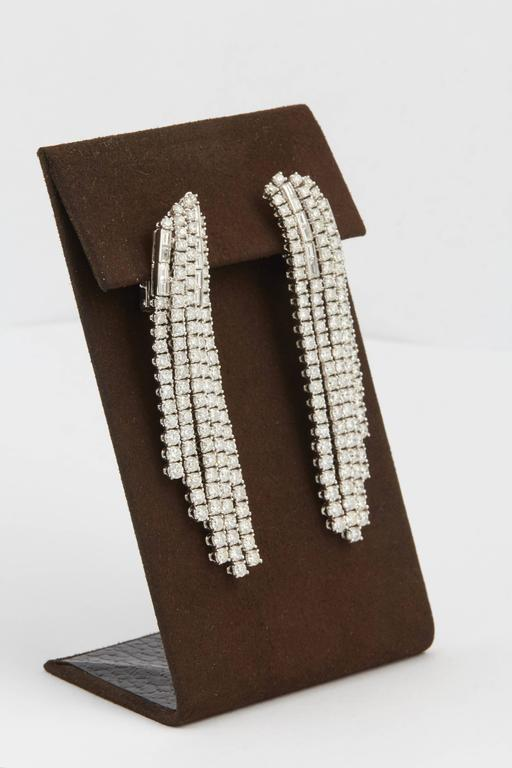 Like a waterfall of diamonds!!  18.41 carats of round brilliant cut diamonds with subtle baguette diamond accents set in 18k white gold.  F/G VS diamonds  A FABULOUS earrings with great movement and presence.  Just over 3 inches long from its