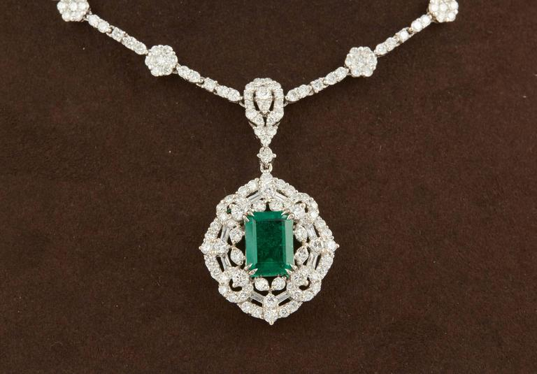 A stunning green emerald and diamond necklace in a classic design.   1.84 carat GIA certified emerald cut Green Emerald.  The emerald is surrounded by diamonds and hangs from a diamond necklace featuring 9.40 carats of diamonds F-G in color.  18k