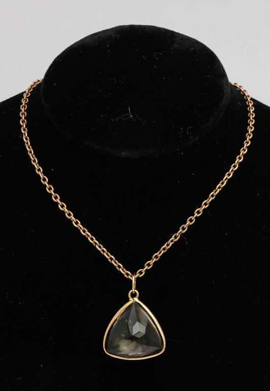 A buff-topped triangular-cut smokey quartz with a faceted reverse, bezel set in yellow gold with gold suspension ring.  Chain not included.   20th century.   Pendant measures ¾ in. (1.9 cm.) from one corner to the next.  Quartz measures 8.7 mm deep.