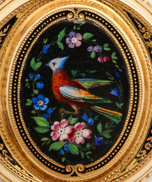 Of 18k gold, depicting a vibrantly colored bird in translucent enamel amidst dense clusters of violet and pink flowers, on a black enamelled ground, enhanced by black and gold stippled and floral decoration, the reverse fitted with an oval glass to
