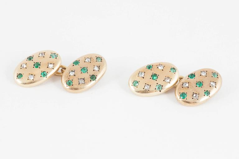 A good quality pair of oval,18ct yellow gold cufflinks,set with 5 emeralds and 4 rose cut diamonds to each oval.french,c,1900,size 16mm x 10mm