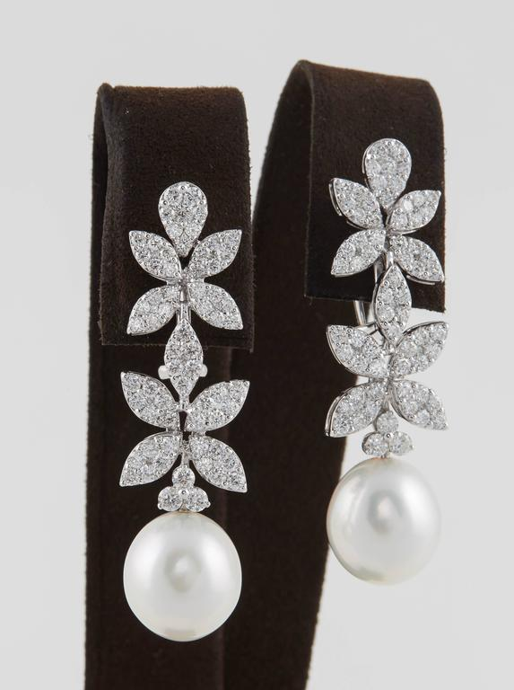 A beautiful pearl and diamond earring with tons of sparkle!  3.37 carats of white round brilliant cut diamonds set into marquise and pear shaped designs.   Approximately 12 mm pearl drop.  18K white gold  The earrings measure approximately 1.88