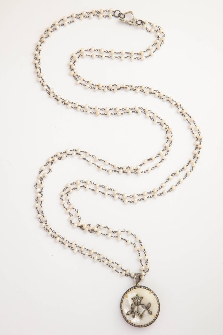This elegant and stylish necklace is two strands of 40 inch freshwater pearl chain.  The pendant is a large dome of Mother of Pearl surrounded by diamonds with a silver and diamond floral center. It can be worn twice around the neck and settle at