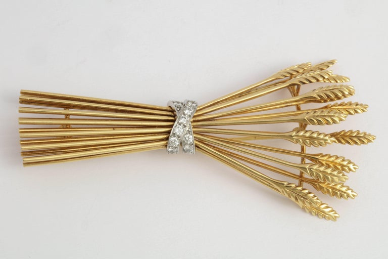 Charming 18kt Yellow Gold stack of 15 Sheaves bundled by a criss cross band set with 11 full cut Diamonds.  Very distinctive.  Marked 750 on the reverse of one sheaf and Tiffany & Co on another. Diamond weight: approx.35pts.  Lightweight and very