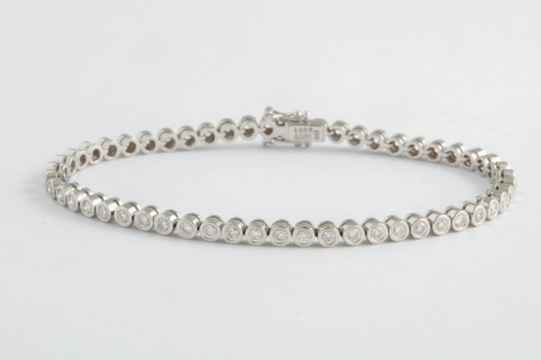 Modern adaptation of the traditional line Bracelet Bezel set in 18kt White Gold w 53 bezel set stones.  Full cut - clean & white stones.  Worn by itself - with a white or yellow gold watch or with a bracelet.  In fact - this bracelet can be worn