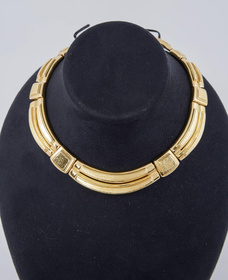 The collar necklace is a striking choker made of large links finely crafted in 18k hammered gold.
