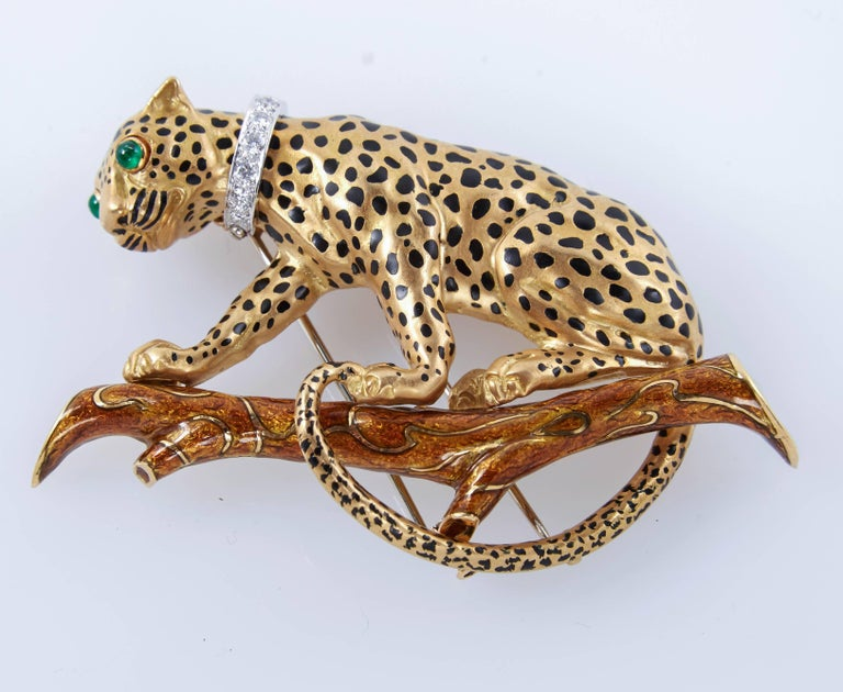 This beautiful leopard brooch is an iconic example of David's Webb nature-inspired designs. Brooch is crafted of 18k yellow gold with black enamel spots. The feline is perched atop a branch of brown enamel. Two cabochon emeralds form its eyes, while
