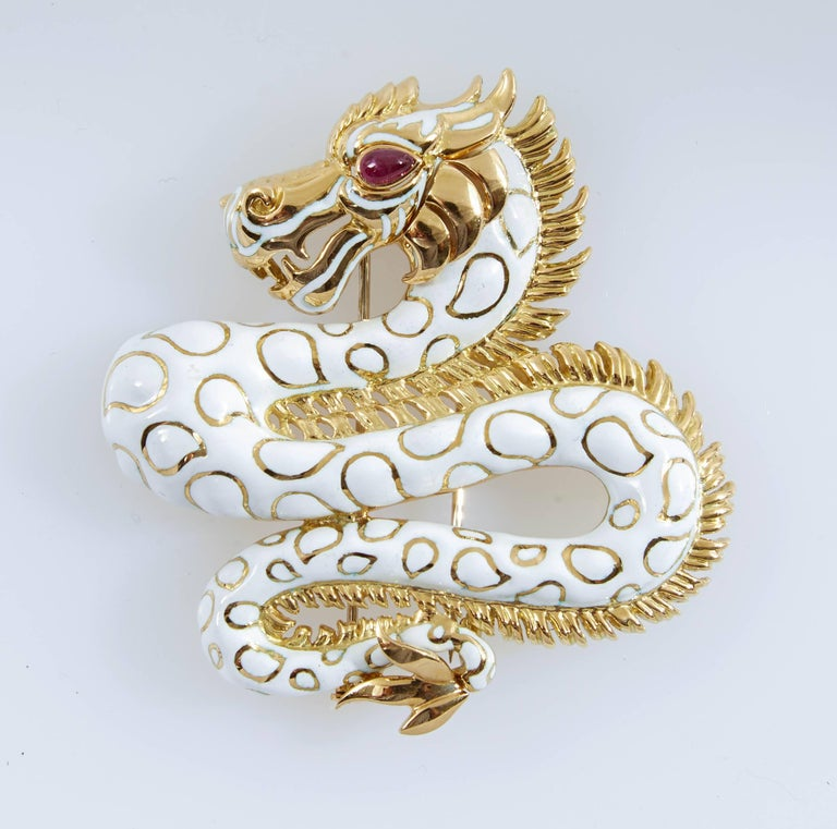 White enamel dragon brooch finely crafted in 18 k yellow gold accented with round brilliant cut Diamonds and cabochon Ruby. Signed David Webb