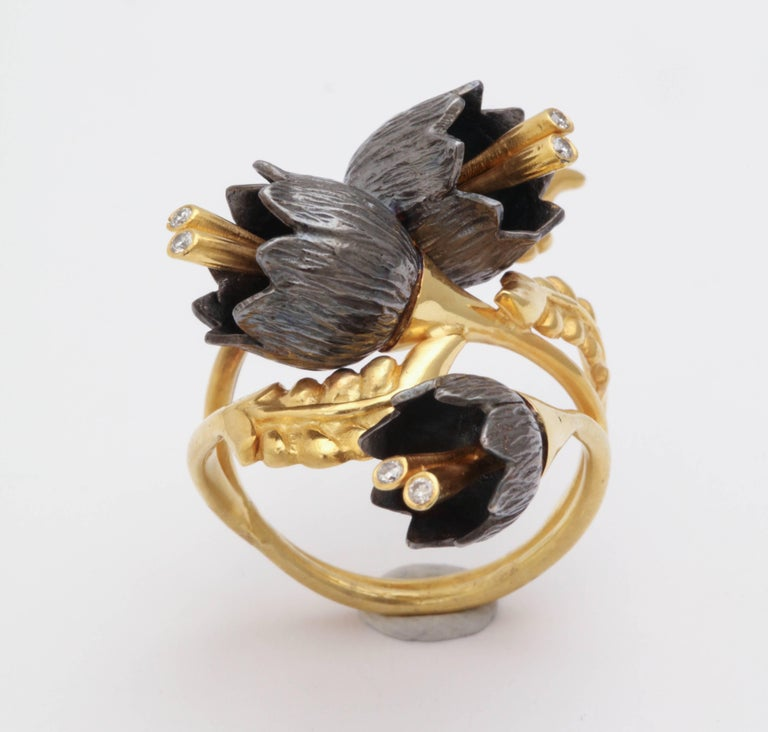 A lily of the valley ring composed of 18kt yellow gold leaves and three rhodium plated sterling silver lily of the valley flowers. The flowers cascade down an 18kt yellow gold vine. Each flower has 18kt yellow gold stamen set with diamonds. Size