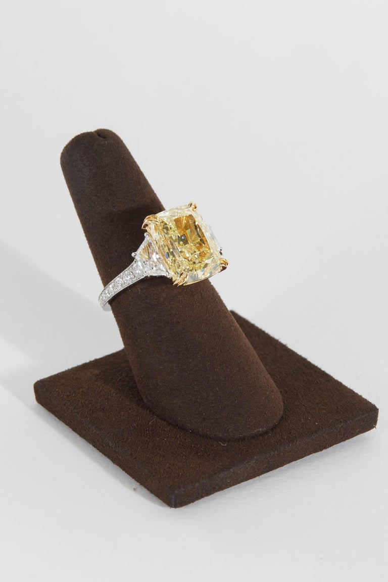 An amazing diamond full of sparkle and brilliance! A rare and most sought after rectangular shape!  GIA certified Fancy Yellow 10.17 carat SI2 center diamond.  1.55 carats of white diamonds set along the side of the center and along the band.