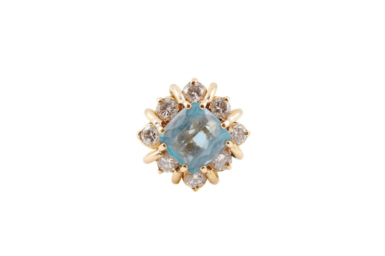 Such a beautiful ring!  You will get compliments on this one for sure!  In 18 karat yellow gold, the 3.00 carat aquamarine is set an an angle and is surrounded by 1.30 carats of diamonds.  The yellow gold mounting is a stunner by itself! Size 5.