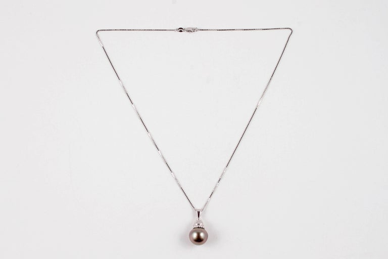 Lovely button shaped, 13.60 mm natural color Tahitian cultured pearl on 18 inch white gold chain.