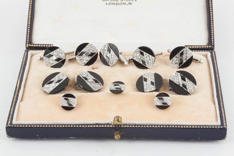 A fine set of French,Art Deco cufflinks,buttons and studs set with Onyx and diamonds.The diagonal lines of diamonds set with two,lozenge shaped onyx,with a baguette cut diamond centre,french marks.c,1930-5