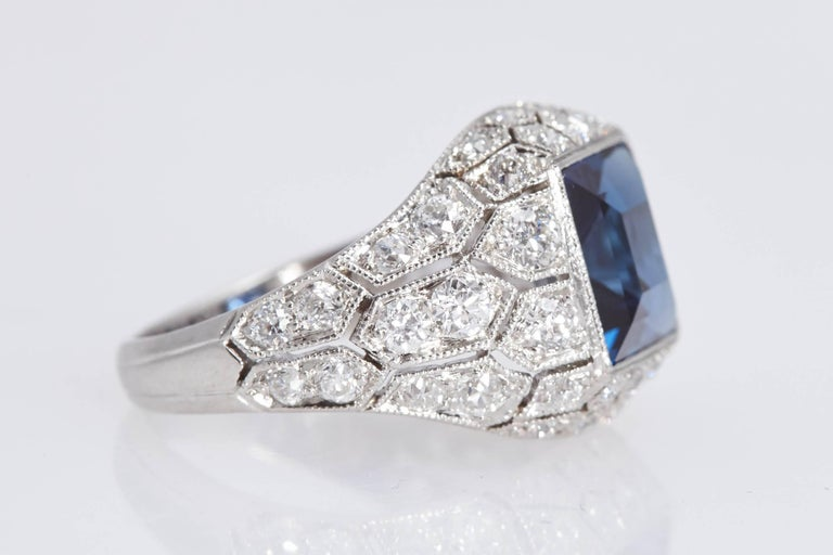 Beautiful Art Deco J.E. Caldwell Sapphire Diamond and Platinum ring. The center blue sapphire is a square shape weighing 2.89 carats and has a certificate from the American Gemological Laboratories. The sapphire is set in a ring with intricate