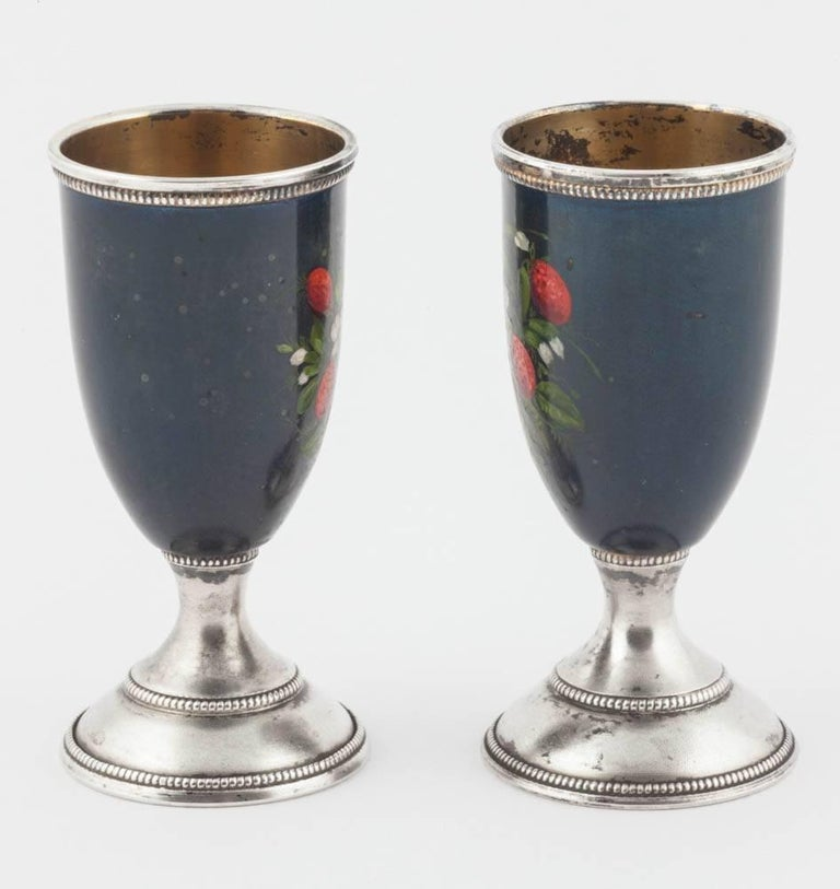 Forecasting spring, a pair of silver cups on pedestal stands, the body of each painted with clusters of wild strawberries against a deep blue background, with beaded borders and gilded interiors.  With Russian hallmarks.  Each cup 2 3/4 in. (10.8