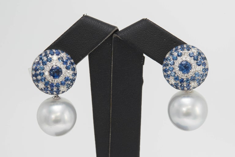 18K White gold earrings featuring two South Sea Pearls measuring 14-15 mm flanked with blue Sapphires weighing 4.90 carats and diamonds weighing 0.63 carats. Color G-H Clarity SI