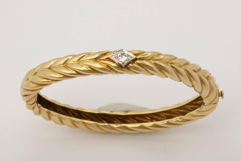 One Ladies 18kt Yellow Gold High Polish Textured Ridged Gold Hinged Oval Shaped Bangle Bracelet. Centering An Approximate .25ct Full Cut Diamond. Bangle Fits An average To Small Size Wrist. Signed And Numbered Cartier, 18kt.Serial # 90032.Attached
