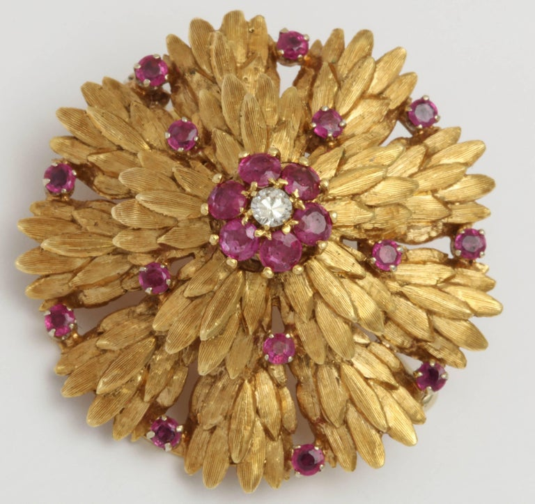 Circular three Dimensional chased 18kt Yellow  Gold Pin set with vivid faceted Rubies and centered with a full cut Diamond surrounded by 6 Rubies. Marked 18kt Italy.  Very chic and very elegant hearkening an age of Suits , White Gloves and a Pillbox