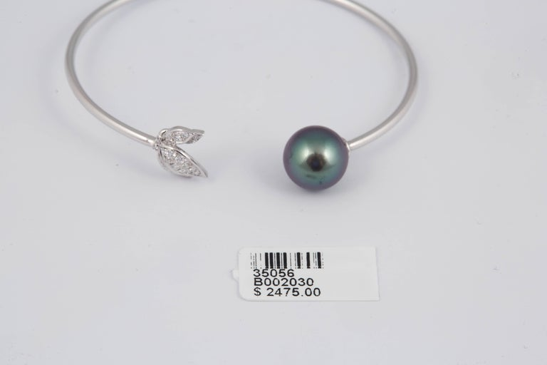 18K White Gold bangle bracelet featuring 23 round brilliants weighing 0.22 Carats and one Tahitian Pearl measuring 11-12 mm.