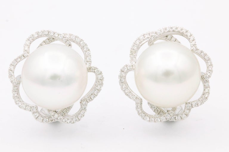 18K White gold earrings featuring two South Sea Pearls measuring 13-14 mm flanked with a diamond floral halo weighing 0.60 carats. Color G-H Clarity SI