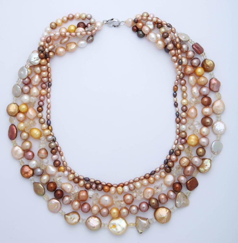 5 Strands of multi color, variations of orange, beige and brown,  and multi shapes and sizes  fresh water pearl necklace. Great colors for any season. Necklace can  be worn flat or twisted. The shortest strand is 18 in. and the longest strand is 21