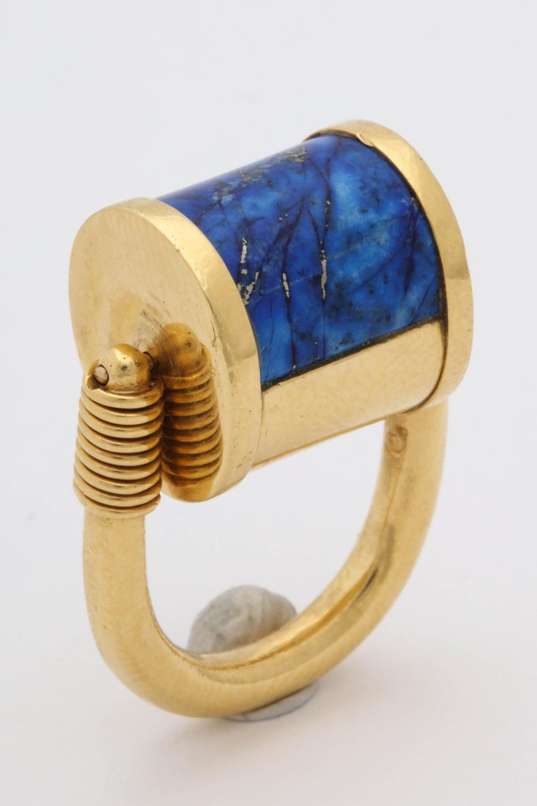One Unisex Unusual Padlock Design Rolltop Reversible Ring Composed Of One Custom Cut Inlaid Lapis Lazuli Stone.This Three Dimensional Ring May Be Rolled Over To Wear On The Gold Side. Ring Created In 22kt Gold Designed By Cellini Jewelers.Current