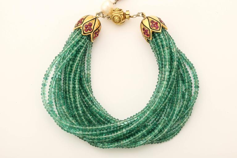 This bracelet has 17 stands and approximately 400 cts of 3 mm beautiful green emerald beads. The clasp is 18 kt yellow gold with 2.78 cts faceted rubies, black enamel. The 'tail' hanging from the clasp is made of fresh water pearls a large oval ruby