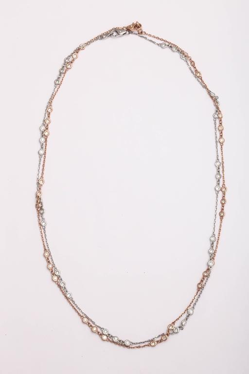 This is an interesting new style for 'diamonds by the yard'. In this necklace the diamonds are grouped in three's with chain in between each set of bezel set diamonds.  The 14 kt rose gold necklace has a total of 1.04 ct of diamonds, 30 stones,G