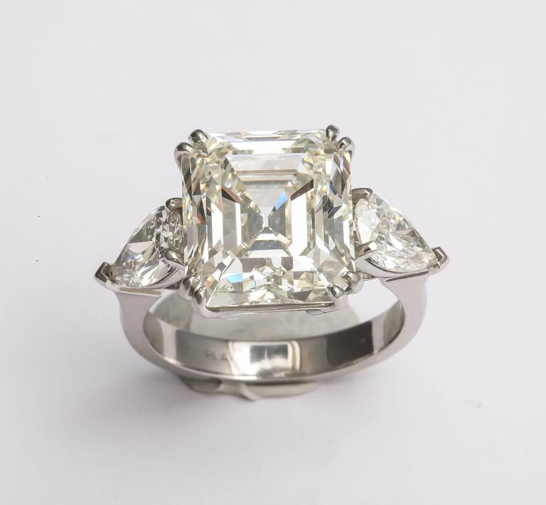 This ring is large and in charge! A dazzling and fine quality center stone is an 8.37ct emerald cut, K  color and VS 1 in clarity. It is provided with an GIA certificate. The metal is platinum and the 2 side pear shapes weigh 1.47 cts together. The