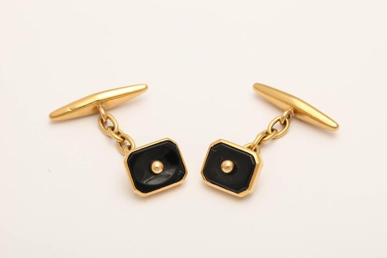 The carved black onyx rectangular links with canted corners in 18k yellow gold, with handmade gold link chains attached to tapered gold bar links.   Hallmark for Porto or Lisbon, mid 20th century  The onyx links-10.7 x 9 mm; the chain ½ in (1.2