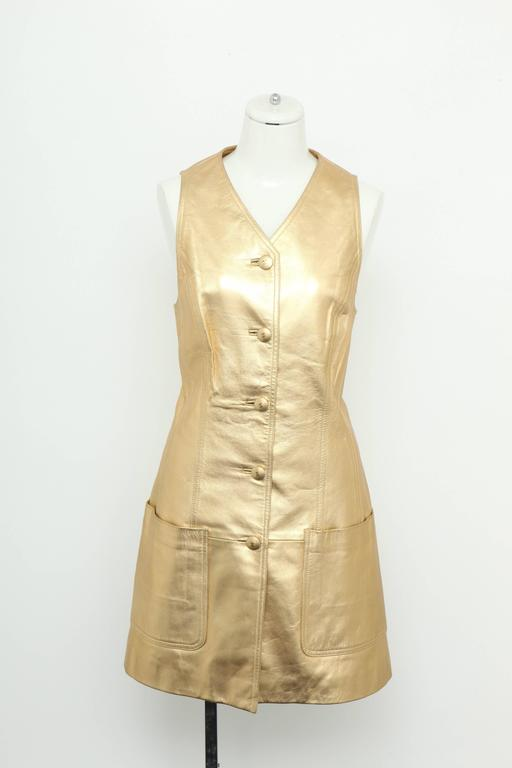 Extremely rare Chanel Gold leather vest dress with CC Buttons. From the 1980's. Belt sold separately.  Size 40 Shoulders: 15 inches Bust: 14.5 Inches Waist: 16 Inches Hip: 32 Inches