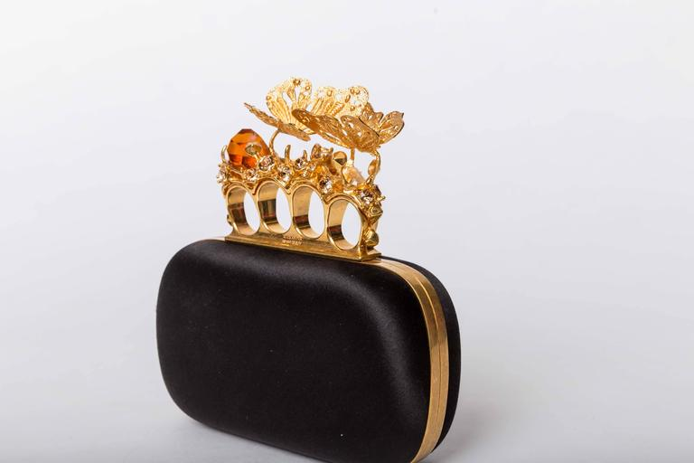 Alexander McQueen Butterfly Knuckle-Duster Box Clutch Bag features golden butterflies perched on large amber colored crystal stones. Trimmed with gilded brass hardware and fitted with iconic Swarovski-studded mini skulls, golden-framed, hard-shell