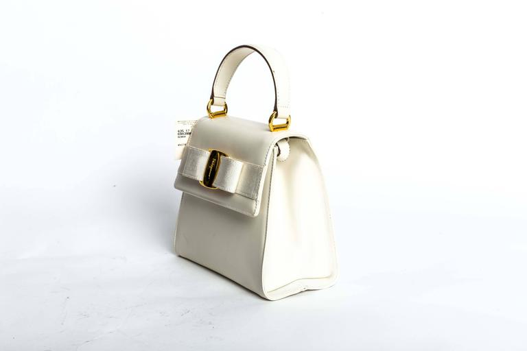 Ferragamo Vintage Vara Bow Two Way Bag in White Leather features gold hardware, grossgrain bow, magnetic closure, interior zip pockets, and removeable leather strap.