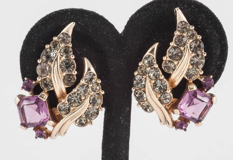 Charming necklace and earrings form Marcel Boucher, composed of a centrepiece at the front with snake chain to the rear. Beautiful square cut deep amethyst paste stones mix with gilt floral leaves, set with sophisticated grey paste, in both the