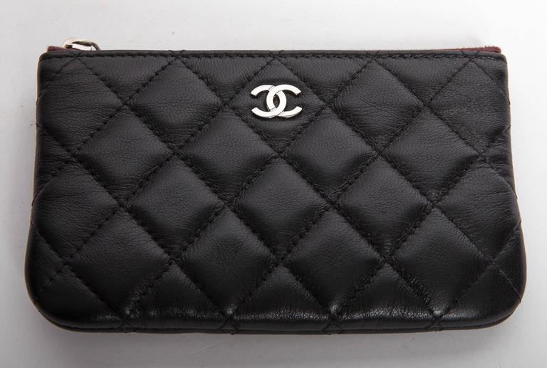 Black Quilted Chanel Makeup Bag with Silver Hardware. Authentication Card is included. No 16933875 denotes the year 2012. Zip opens to reveal a quilted nylon interior. Zip pull is claret colored leather. Pristine condition inside and out.